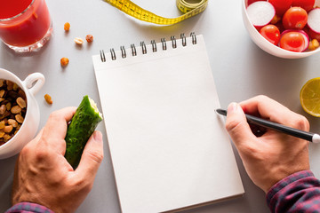 losing weight man writes in a notebook how many calories he ate
