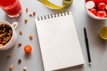 notebook with place for text to write calories and fresh vegetables on a white background