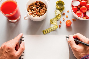 healthy eating, measuring tape and man writing calories in a notebook