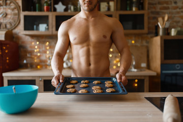 Nude man cooking pastry on the kitchen