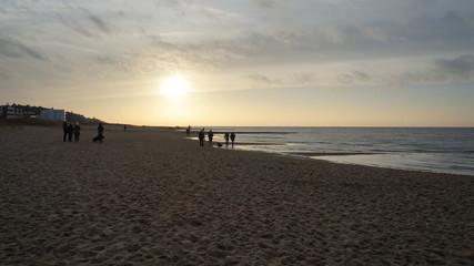 Strand mit Abendämmerung und ein paar Menschen am Wasser