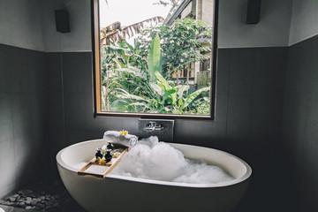 Obraz Bath with foam is filling with water, beauty products on bathtub. - fototapety do salonu