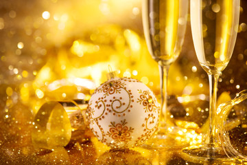 Holiday Champagne Flute over Golden glow background. Christmas and New Year celebration. Two Flutes...