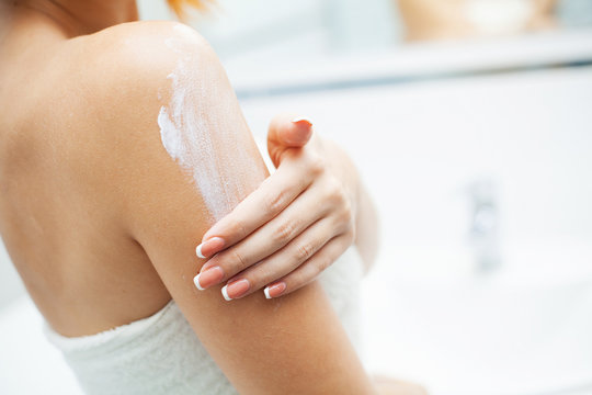 Skin care. Woman use skin care products at home in light bathroom