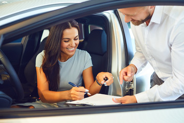 A young woman buys a car in a car showroom. Fototapete