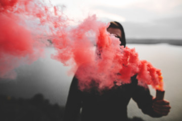 Red smoke bomb. Blurred image of ultras hooligan holding  smoke bomb in hand, standing on top of rock mountain with amazing view on river. Atmospheric moment. Copy space