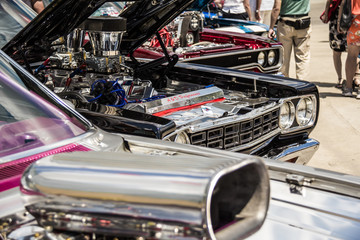 Heavily worked on muscle cars with their hoods open and engines exposed on display at a car show.