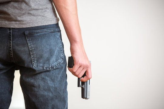 Man holding a gun in his hand with white background, rear view.