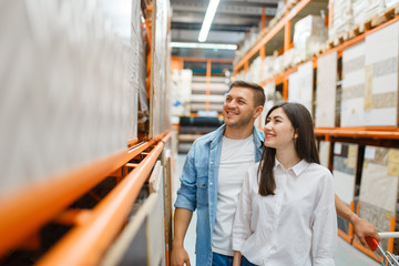 Young couple choosing ceramic tile, hardware store