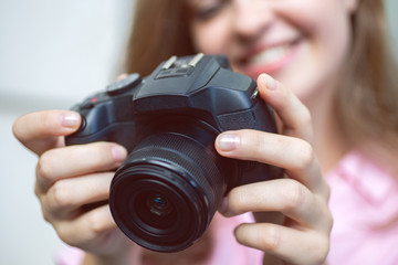 Smiling caucasian woman photgrapher holding a digital camera in hands close up, taking a photo or video
