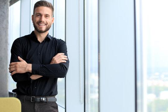 Modern business man is standing near window in the office