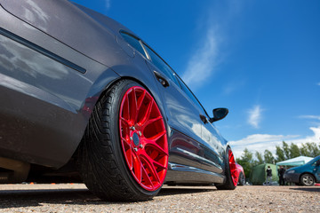 Gray car with lowered suspension and bright red forged wheels is on the parking. Against blue sky