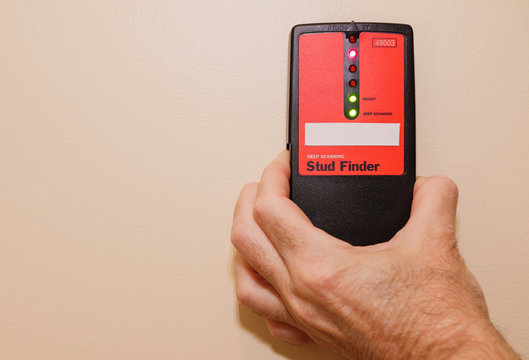 Male carpenter using electronic stud finder to locate interior wall stud.