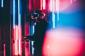 Young man using joystick in hands and VR headset on head playing in dark interior illuminated neon light. Shoting through colored flare on foreground.