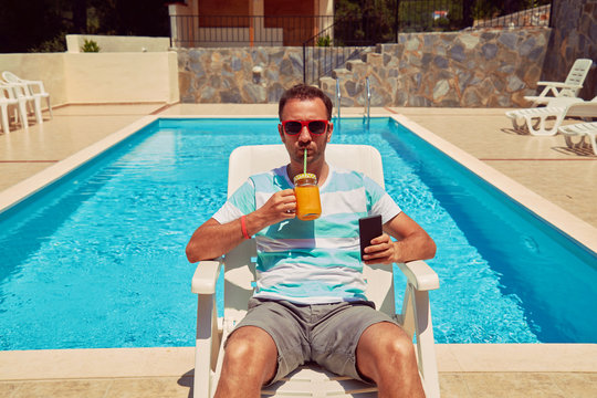 Attractive man using cellphone while drinking juice near swimming pool.