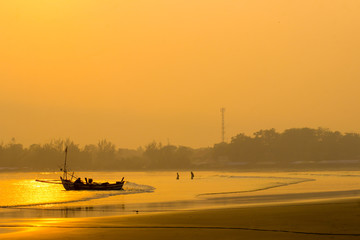 indonesia travel destination, morning fisherman activity in the beach wih beauty water color yellow of sunrise