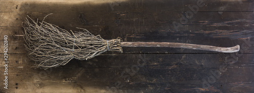 halloween witch broom on black wooden background
