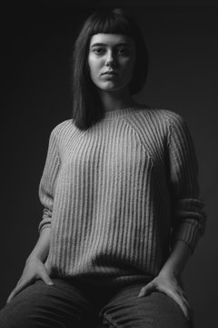 Studio portrait of young woman in sweater. Black and white