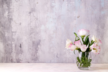 Foto op Canvas Bloemen Eustoma flowers in vase on table near stone wall, space for text. Blank for postcards