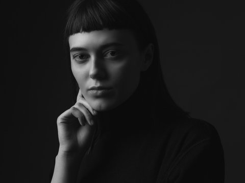 Close up portrait of young woman. Black and white. Low key