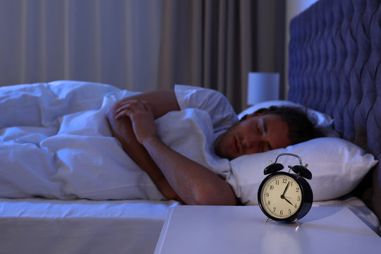 Alarm clock on nightstand near sleeping young man. Bedtime