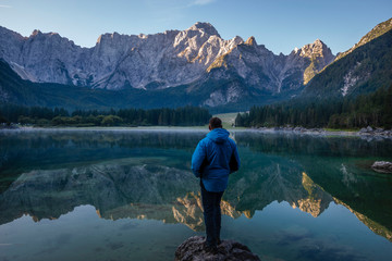 Wall Mural - traveler admiring the alpine lake during sunrise