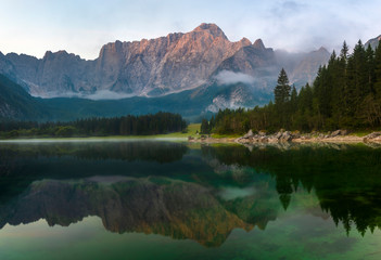 Wall Mural - Panorama of the beautiful mountain Laghi di Fusine lake in Italy during sunrise.Alpine peaks lit by the rising sun reflecting in the water