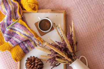 Fall layout with an infinity scarf in double crochet pattern on a wooden tray next to a ball of yarn, a cup of coffee and a vintage vase with dried summer wildflowers. DIY fashion project.