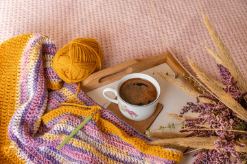Cozy autumn decor with a crocheted scarf in progress in saffron, sunlight yellow, pink and lavender purple colors. Relaxing at home on a fall day, concept. DIY fashion project.