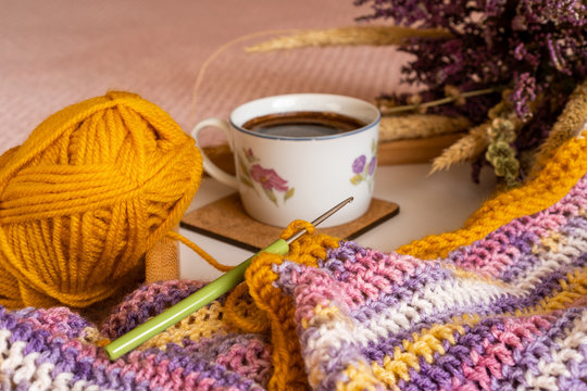 Closeup of a colorful handmade infinity scarf in an autumn decor next to a cup of hot coffee and a bouquet of dried wildflowers. Double crochet pattern. Hand work in progress.