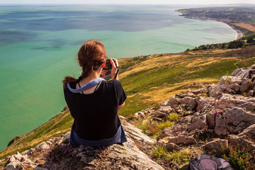 Young woman sitting on a cliff and taking pictures of the stunning Irish coastal landscape on a sunny summer day. Hiker enjoying the view from the mountain top.