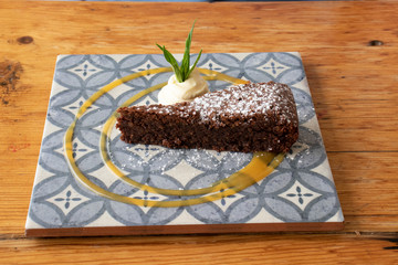 Chocolate cake served on a blue tile