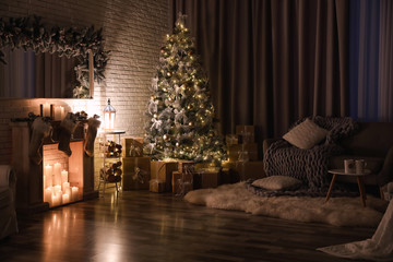Stylish interior with beautiful Christmas tree and artificial fireplace at night