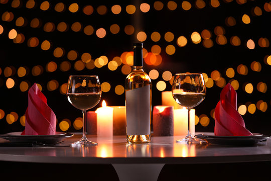 Romantic table setting with bottle of wine and burning candles against blurred background