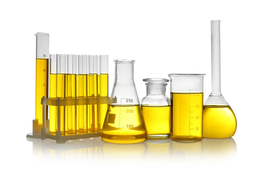 Laboratory glassware with yellow liquid on white background