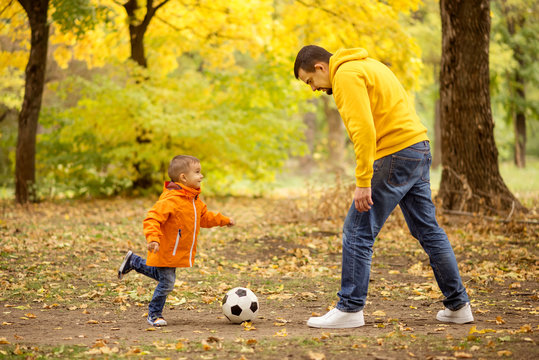 Father and little toddler son having fun in autumn park: dad and child playing football outdoors, kid raised leg ready to kick soccer ball. Active happy family and healthy parenting concept