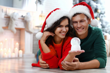 Happy couple with snow globe on floor at home