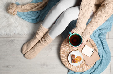 Woman and cup of hot winter drink on floor at home, top view