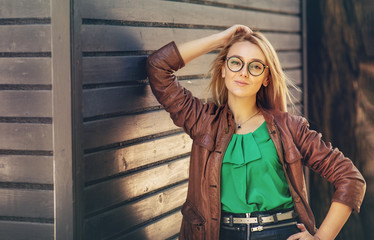 Outdoor fashion portrait of a young fashionable woman with spectacles wearing autumn outfit