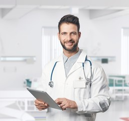 Confident happy doctor with tablet in hospital