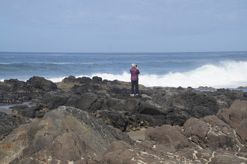 Woman taking pictures of oncoming surf