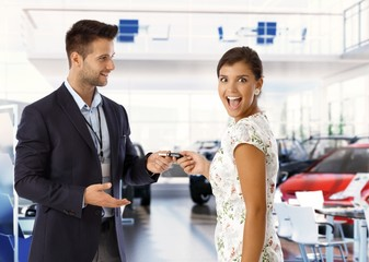 Excited young lady is getting keys for new car