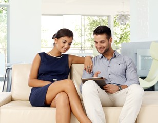 Young couple at home browsing internet with tablet