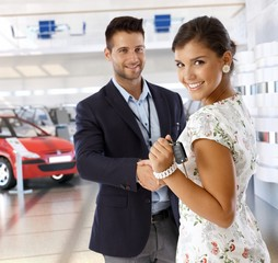 Young businesswoman shaking hands with car dealer