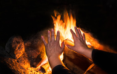 Blazing bonfire and old lonely woman in detail on night black background. Female hands with fingers splayed over warm fire with orange burning flames. Tranquil scene of evening rest. Selective focus.