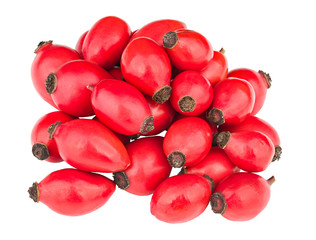 Pile of red rose hips isolated on white background. Detail of fresh ripe rosehips. Heap of sweet organic briar fruits with healthy vitamins and carotenoids. Used in herbal tea or alternative medicine.