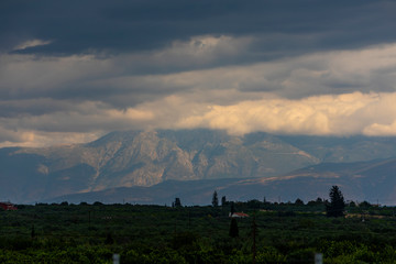 A mountain range in Greece covered in low hanging cloud.