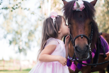 Little girl in a beautiful dress of pink color in the park with a brown pony.