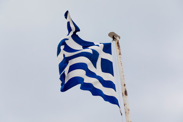 The Greek flag flying in the wind on a white flag pole.