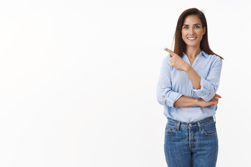 Motivated good-looking adult female employee curiously pointing left, introduce sideways copyspace, smiling joyful, discuss project with coworkers, stand blue-collar shirt white background